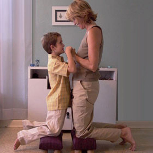 Mother and son kneeling on a kneeler holding hands and smiling