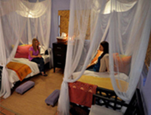 Two girls that are sitting on a separate canopy beds with white sheer linens