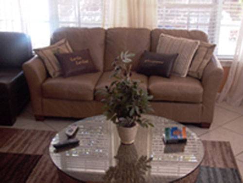 A light leather couch with five assorted pillows and a glass coffee table
