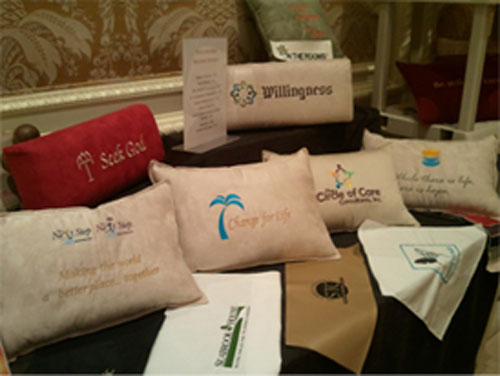 Six assorted pillows with different messages on each pillow displayed on a table