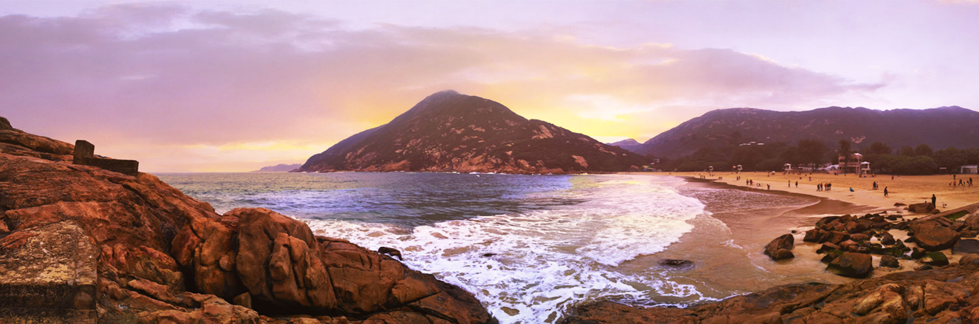 Sunsetting behind the mountains with a view of the waves coming in on the beach