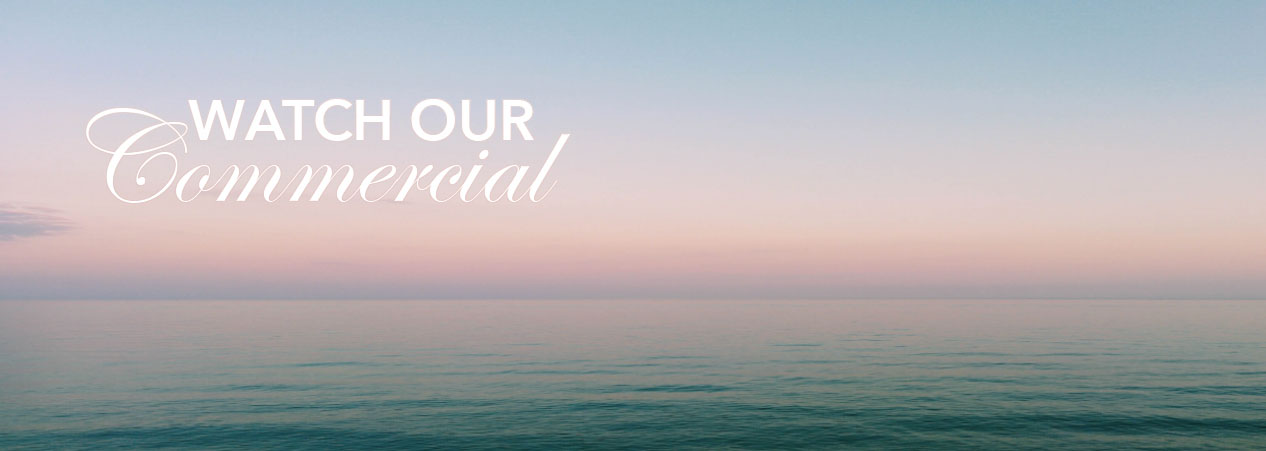 Text reads Watch Our Commercial in white letters with a background of a dark teal colored ocean and a pale pastel sky